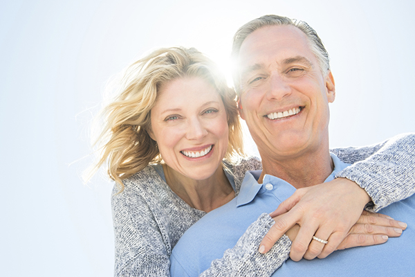 Janice Pliszczak dds dentist in syracuse NY mature couple hugging in the sun 187007308