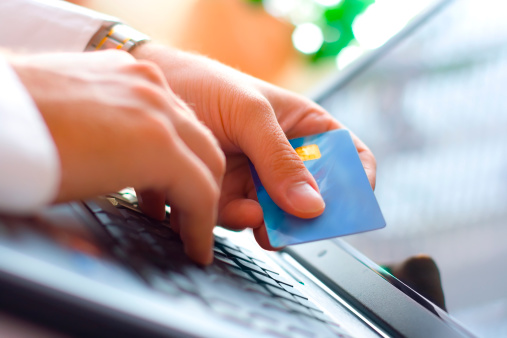 Image of hands holding a credit card and making a payment online