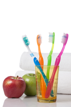 Glass full of colorful toothbrushes and apples